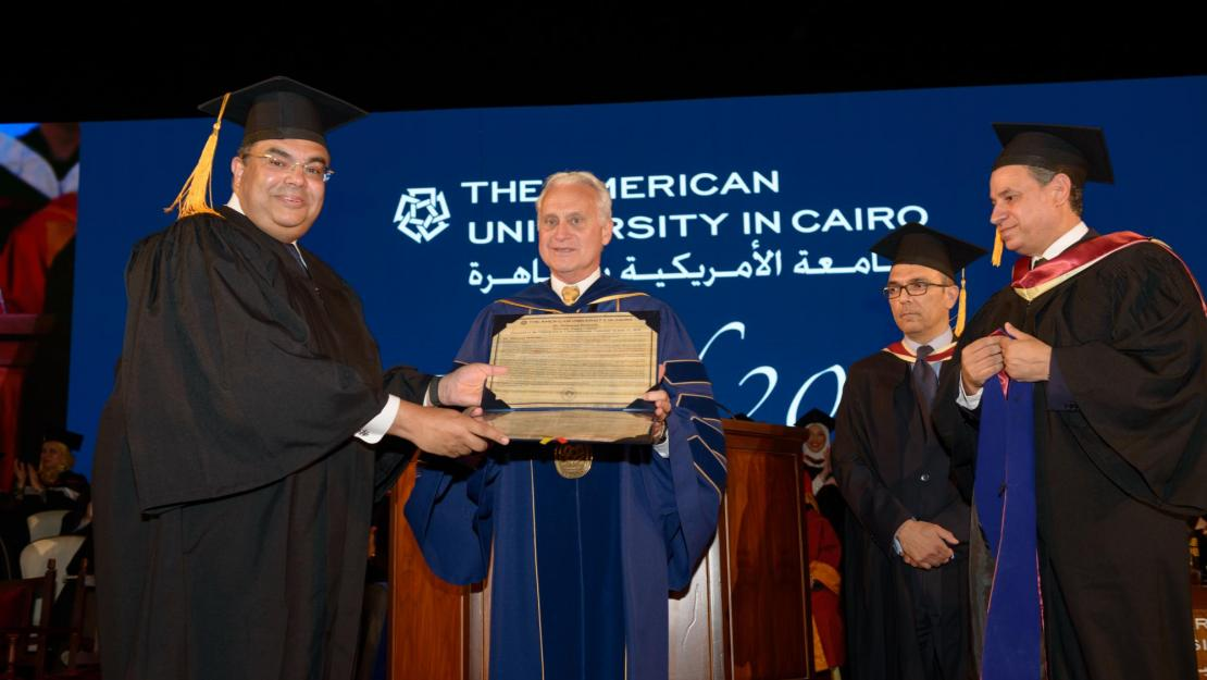 President Francis J. Ricciardone presents Mahmoud Mohieldin, Senior Vice President for the 2030 Development Agenda, United Nations Relations and Partnerships, World Bank Group and the undergraduate keynote speaker, with honorary doctorate degree