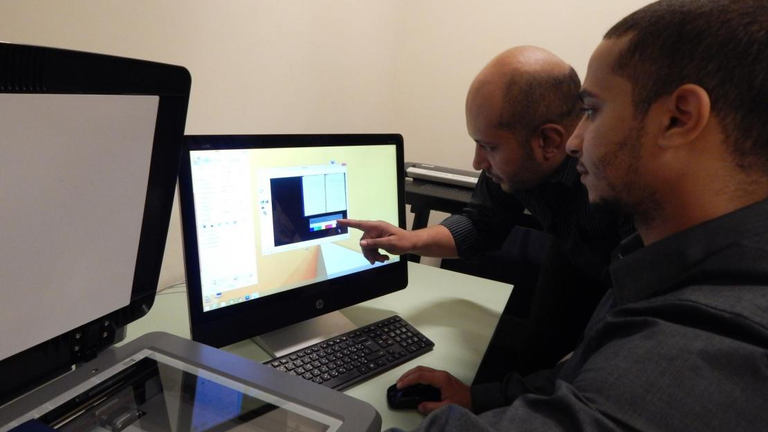 Mohamed Abdel Rehim and Mohammed Saleh scan books for AUC Library's new project with Arabic Collections Online