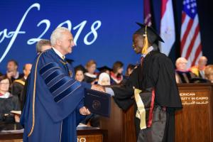 AUC President Francis Ricciardone shakes hands with a graduate student receiving his diploma